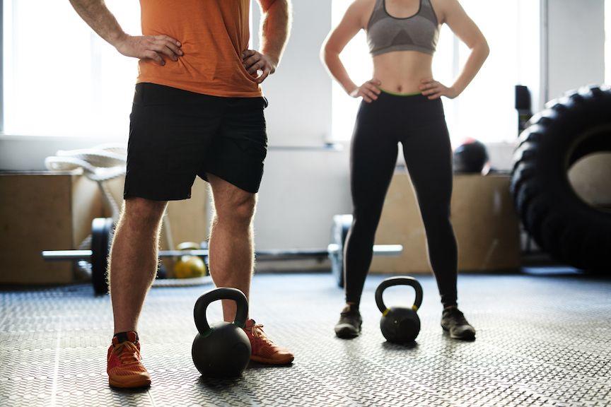 hombre y mujer entrenando con pesas rusas