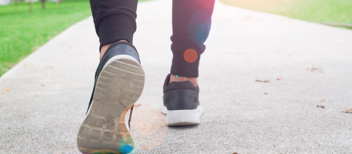 fitness woman walking in public park, closeup on shoe with sunlight